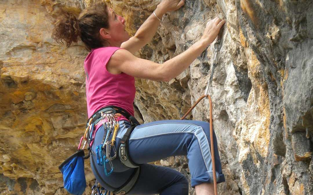 A woman climbing a sheer rock face with determination on her face to illustrate the way we can break through our fear to acheive formally impossible things